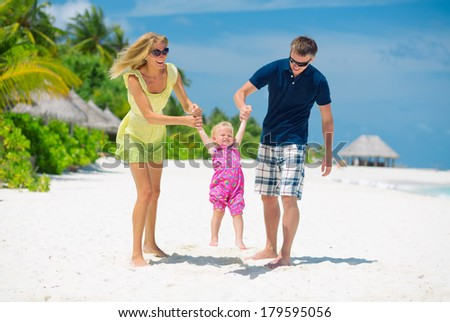 Happy family having fun on the white sandy beach on Maldives. Family of three having tropical vacation.  - stock photo