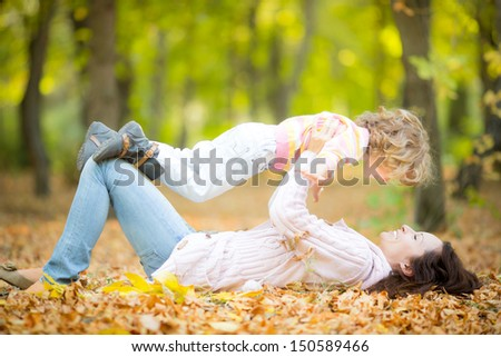 Happy family having fun outdoors in autumn park against blurred leaves background