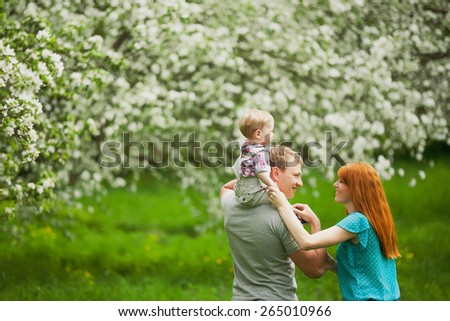 Happy family having fun outdoors in spring blooming garden. Father, mother and child. Family concept. Picnic. Woman, man holding little boy in hands. Laughing, smiling people playing with son - stock photo