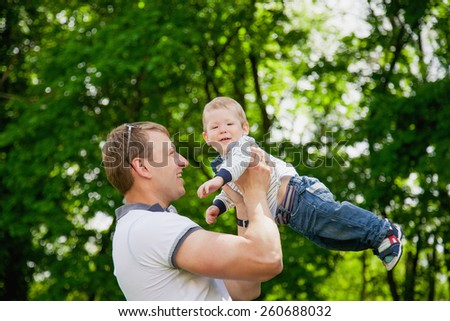 Happy family having fun outdoors in spring garden. Father playing with child. Family concept. Picnic. Man holding little boy in hands. Laughing, smiling people.  - stock photo