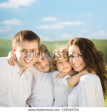 Happy family having fun outdoors in spring green field against blue sky background - stock photo