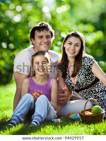Happy family having fun outdoors in spring park against natural green background - stock photo