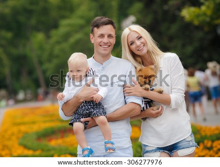 happy family having fun outdoors. Mother, father, child boy and dog having fun in green park.  - stock photo