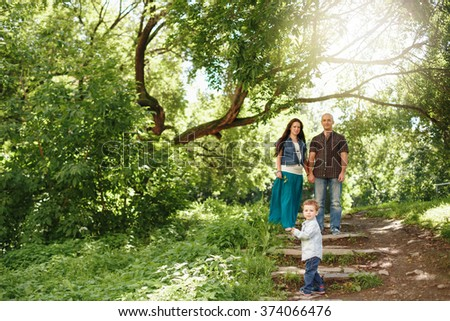Happy Family Having Fun Outdoors. Pregnant Woman, Man and Cute Little Boy. Natural Colors. Selective Focus on a Kid. - stock photo