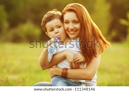 happy family having fun. son drinking water from the plastic bottle, mother holding him. outdoor shot. - stock photo