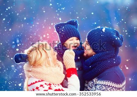 happy family having fun under winter snow, holiday season - stock photo
