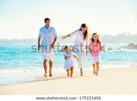 Happy family having fun walking on the beach - stock photo