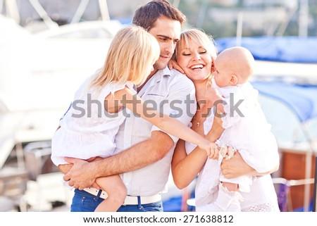 Happy family having fun walking on the mooring near yachts - stock photo
