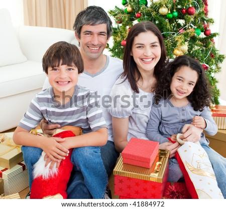 Happy family having fun with Christmas presents - stock photo