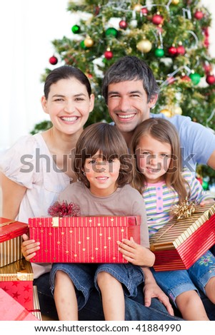 Happy family having fun with Christmas presents - stock photo