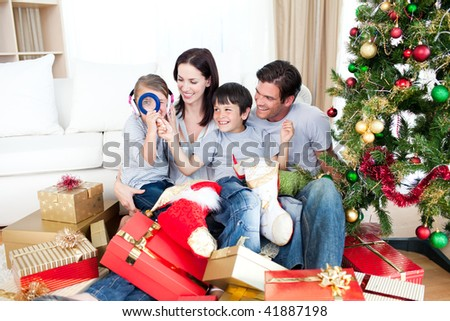 Happy family having fun with Christmas presents at home - stock photo