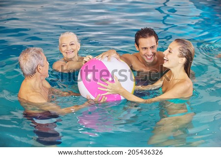 Happy family having fun with water ball in swimming pool in summer - stock photo