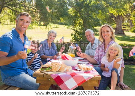 Happy family having picnic and holding american flag on a sunny day - stock photo