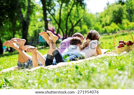 Happy family having weekend in summer park - stock photo