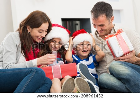 Happy Family Holding Christmas Gift - stock photo