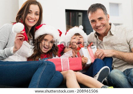 Happy Family Holding Christmas Gift Looking At Camera - stock photo