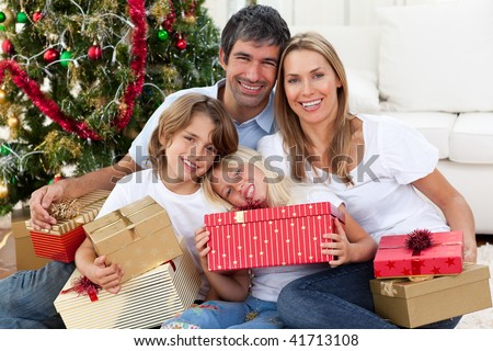Happy family holding Christmas gifts and sitting on the floor - stock photo