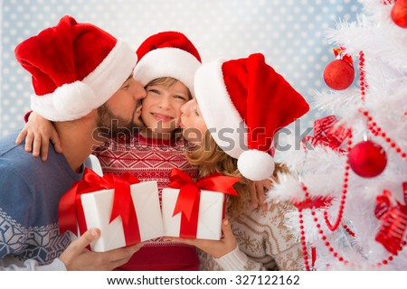 Happy family holding Christmas gifts near Xmas tree. Child, mother and father having fun at home - stock photo