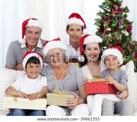 Happy family holding Christmas presents at home - stock photo