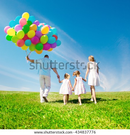 Happy family holding colorful balloons. Mom, dad and two daughters playing on a green  meadow.  - stock photo
