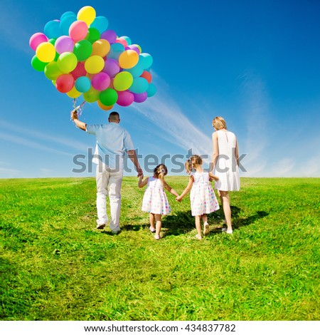 Happy family holding colorful balloons. Mom, dad and two daughters playing on a green  meadow.