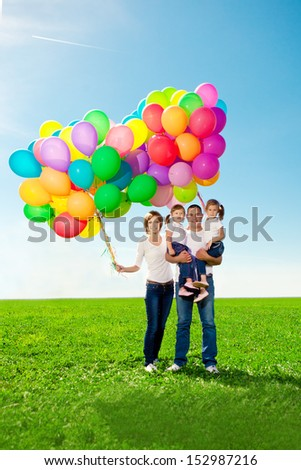 Happy family holding colorful balloons outdoor. Mom, dad and two daughters playing on  a green meadow.   - stock photo