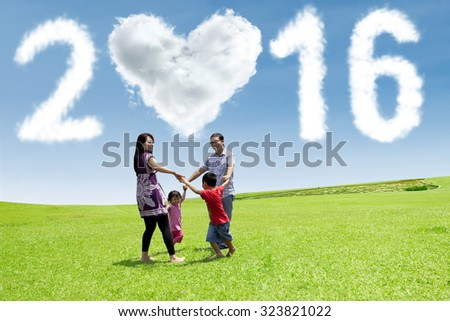 Happy family holding hands together and playing on the field while celebrating new year with cloud shaped 2016