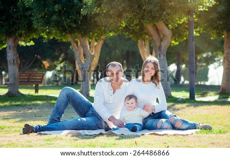 happy family holiday. Young parents and little kid sitting on grass in the park. - stock photo