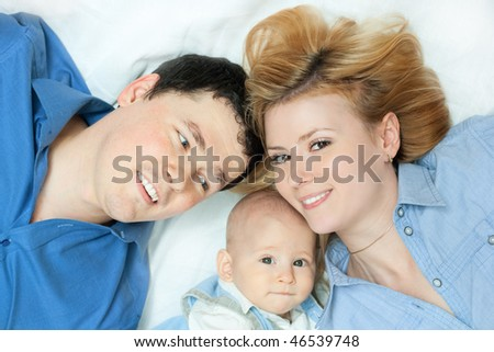 happy family home: father, mother and baby lying down on white - stock photo