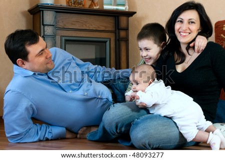 happy family home: father, mother, son and baby lying on the floor and playing