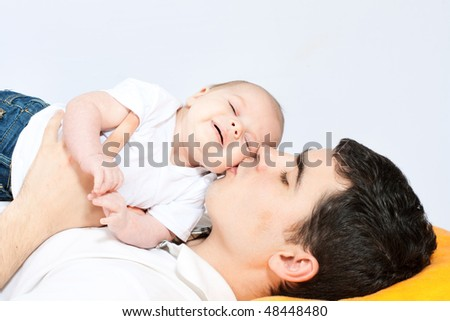 happy family home: father playing with his little baby