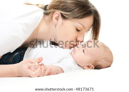 happy family home: mother and baby lying on the bed and playing - stock photo