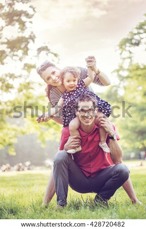 Happy family hugging in a park - stock photo