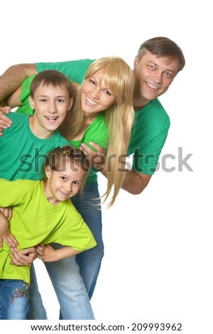 Happy family in a green clothes standing in studio