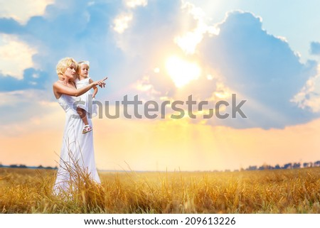 Happy family in a meadow. Mother holds child on hands on a background of a beautiful sunset in the field. Woman points a finger in the free space on the photo. - stock photo