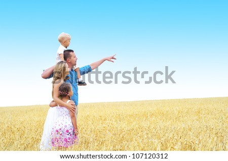 happy family in a wheat field - stock photo