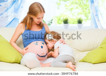 happy family in anticipation of the baby. Pregnant mother and child daughter paint colors on the tummy - stock photo