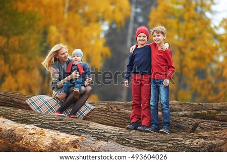 Happy family in autumn on the nature. Young mother and her sons. Two brothers are hugging.