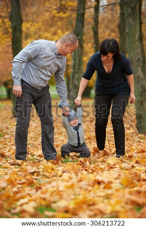happy family in autumn park on yellow leaves - stock photo