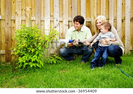 Happy family in backyard watering plant with hose - stock photo