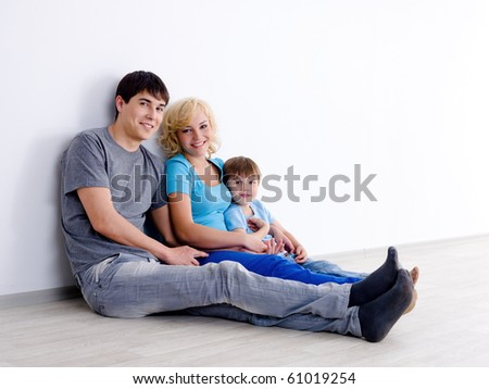 Happy family in casuals with little son sitting on the floor in empty room - indoors - stock photo