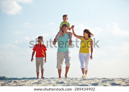 Happy family in casualwear walking on sandy beach - stock photo