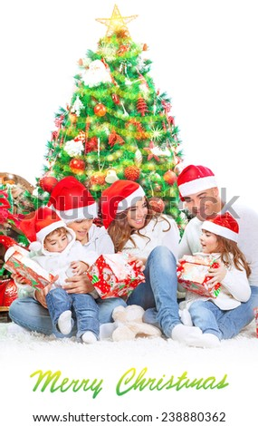 Happy family in Christmas eve at home sitting near decorated fir tree over white background, wearing red Santa hats opening presents, happiness and togetherness concept - stock photo