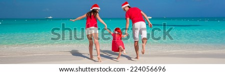 Happy family in Christmas Hats having fun on white beach - stock photo