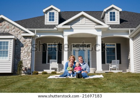 Happy Family in Front of Their Home - stock photo
