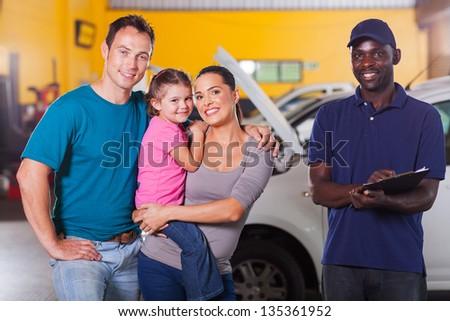 happy family in garage with auto mechanic - stock photo