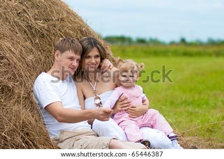 Happy family in haystack or hayrick - stock photo