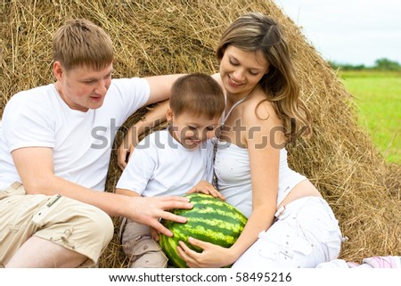 Happy family in haystack or hayrick with watermelon - stock photo