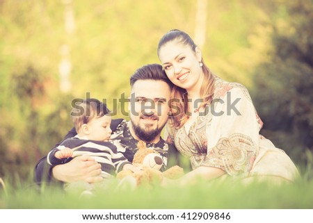 Happy family in park in warm sunny day. Mother, father and son