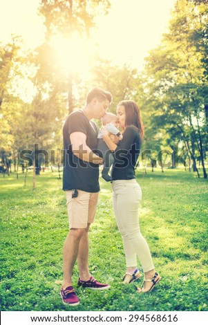 Happy family in park, mother and father holding and kissing a few months old son, kid. Infant portrait and happy family concept in park - stock photo